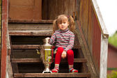 Lovely little girl posing sitting near the Russian Samovar on the porch of the farmhouse. — Stock Photo