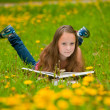 A girl reads a book in the meadow — Stock Photo