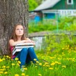 Tired school girl in the park with books. — Stok fotoğraf