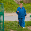 Photo: Active old woman nordic walking outdoors