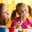 Girl playing with painting with sister. — Стоковое фото