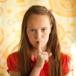 Young girl with her finger over her mouth. — Stock Photo