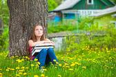 Unavený školačku v parku s knihami. — Stock fotografie