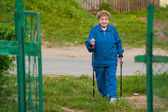 Active old woman nordic walking outdoors — Stock Photo