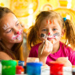 Стоковое фото: Young funny sisters playing with painting