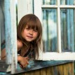 Beautiful little girl looks out the window rural house — Stock Photo