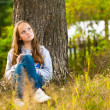 Beautiful teen-girl writing in a notebook while sitting in the park - Стоковая фотография