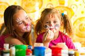 Jonge grappige zusters spelen met schilderij — Stockfoto