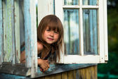 Beautiful little girl looks out the window rural house — Stok fotoğraf