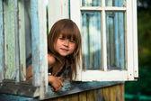 Vacker liten flicka ser ut fönster lantligt hus — Stockfoto