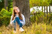 Beautiful teen-girl writing in a notebook while sitting in the park — Stock Photo