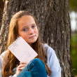 Teen-girl shows notebook while sitting in the park — 图库照片
