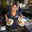 Unknown vendors prepare food at a street side restaurant — ストック写真