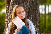 Teen-girl shows notebook while sitting in the park — Stock Photo