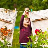 Tatlı beş yıllık kız clothespin ve clothesline — Stok fotoğraf