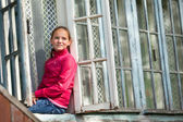 Teen-girl looks out the window rural house. — Stock Photo