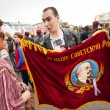 Постер, плакат: An opposition supporter holds a Soviet era flag