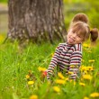 Stock Photo: Little lovely girl playing in the park, shows the language (looking at the camera)