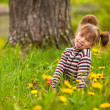 Little lovely girl playing in the park, shows the language (looking at the camera) — Stock Photo