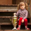 Funny lovely little girl posing sitting near the Russian Samovar on the porch of the farmhouse. — Stock Photo #13123207