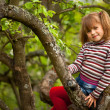 Little girl posing sitting on a tree in the garden. — Stock Photo