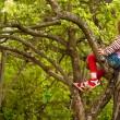 Lovely little girl posing sitting on a tree in the garden — Stock Photo