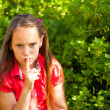 Little girl with her finger over her mouth, hushing. — Stock Photo #13123274