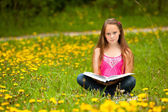 Girl (looking at the camera) reads a book in the meadow — Stock Photo