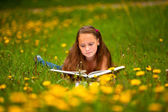 Young girl reading a book while lying in the grass — Stock Photo