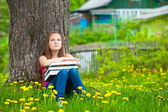 Tired young girl in the park with books. — Stockfoto