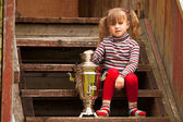 Funny lovely little girl posing sitting near the Russian Samovar on the porch of the farmhouse. — Stock Photo