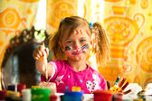 Beautiful little girl artist with paint of face — Stock Photo