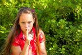 Little girl with her finger over her mouth, hushing. — Stock Photo