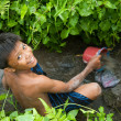 Stock Photo: Poor kid catches small fish in a ditch near a rice field