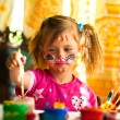 Little girl drawing paint with paint of face — Stock Photo