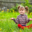 Lovely emotional five-year girl sitting in grass. — Стоковая фотография