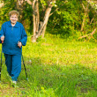 Active woman (85 years old) nordic walking outdoors. — Stock Photo