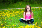 Teen-girl (looking at the camera) reads a book in the meadow — 图库照片