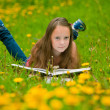 A girl 11 years old reads a book in the meadow — 图库照片