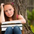 Tired school girl in the park with books — Stockfoto