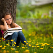 Tired of school girl in the park with books — Stock Photo