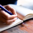 Close-up of hand pen writes in a notebook (blurred) — Stock Photo #15641929