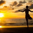 Stock Photo: Young woman practicing yoga on the beach at sunset.
