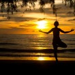 Young woman practicing yoga on the beach at sunset. — Foto de Stock