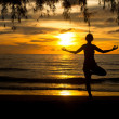 Young woman practicing yoga on the beach at sunset. — Stok fotoğraf