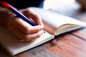 Zbliżenie z piórem strony pisze w notatniku (niewyraźne) — Zdjęcie stockowe