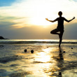 Stock Photo: Young woman practicing yoga on the beach at sunset