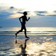 Young woman jogging on the beach at sunset — Stock Photo #15729675