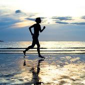 Mujer joven de jogging en la playa al atardecer — Foto de Stock