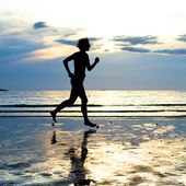Young woman jogging on the beach at sunset — Stock Photo